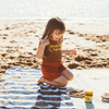 Little girl kneeling on a towel at the beach making a sandwich. The girls wears a Happy little vegemite girls retro T-shirt by Lacey Lane