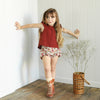 Little girl wearing a red ruffle sleeved top by Lacey Lane