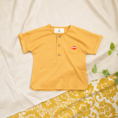 Flatlay of yellow mustard kids retro shirt with iconic embroidered vegemite patch by kids clothing brand MBJ