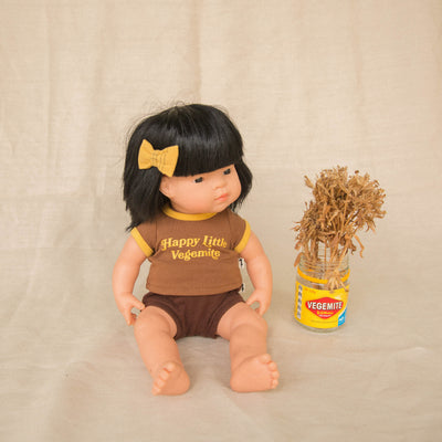 Retro dolls outfit by Lacey Lane on a Miniland Asian doll. A brown dolls ringer tee with mustard trims and slogan Happy Little Vegemite. The baby doll has a matching bow in its hair.