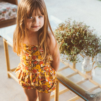 Little girl standing in the sunlight wearing a brown, yellow and red floral top by Lacey Lane