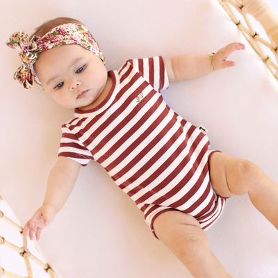 Pretty baby wearing stripped jersey romper by lacey lane. Styled with floral headband.