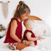 Big sister kissing little sisters head wearing red ruffle sleeved top