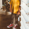 Young boy modelling My Brother John's Bowie stripe jeans from the Happy Little Vegemite Collection paired with a mustard slouch tee. Super retro and vintage boys fashion