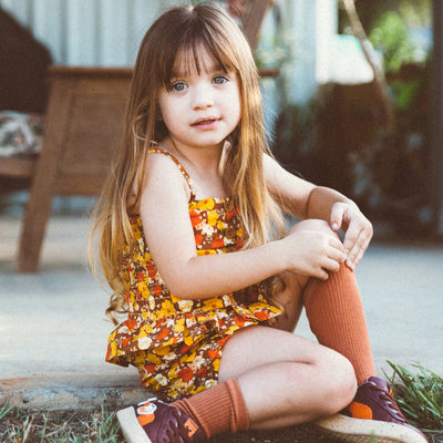 little girl sitting in the grass wearing a girls cami top and girls bloomers by Lacey Lane