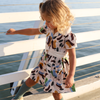Cute little girl wearing vintage inspired dress with large floral print.