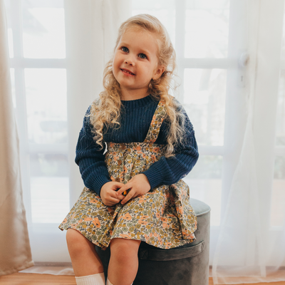 Cute little girl wearing vintage inspired outfit by lacey lane. Sweet navy knit jumper styled with floral suspender skirt