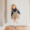 Cute little girl wearing navy blue knit jumper with floral vintage inspired lacey lane suspender skirt
