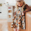 Cute little girl wearing vintage style lacey lane dress with vintage floral design.