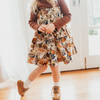 Little girl wearing lacey lane vintage floral design dress styled with brown lacey lane skivvy / turtle neck and cute vintage look shoes and socks