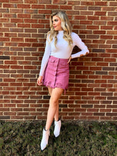 Load image into Gallery viewer, Blonde woman wearing a dusty pink distressed hemline skirt with buttons and pockets