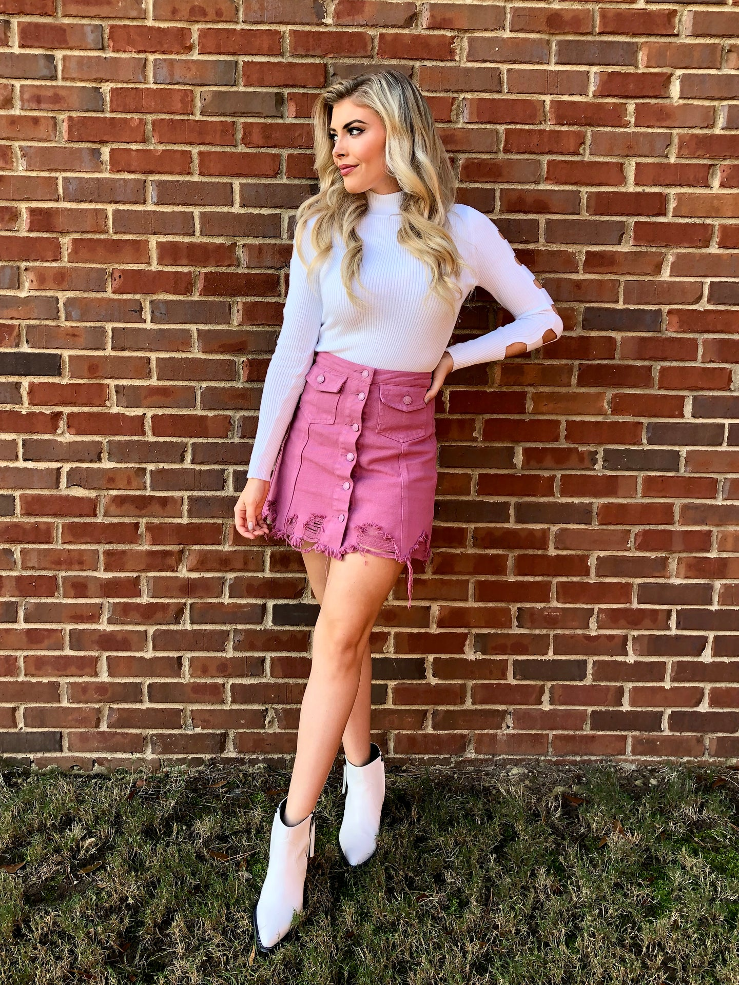Blonde woman wearing a dusty pink distressed hemline skirt with buttons and pockets