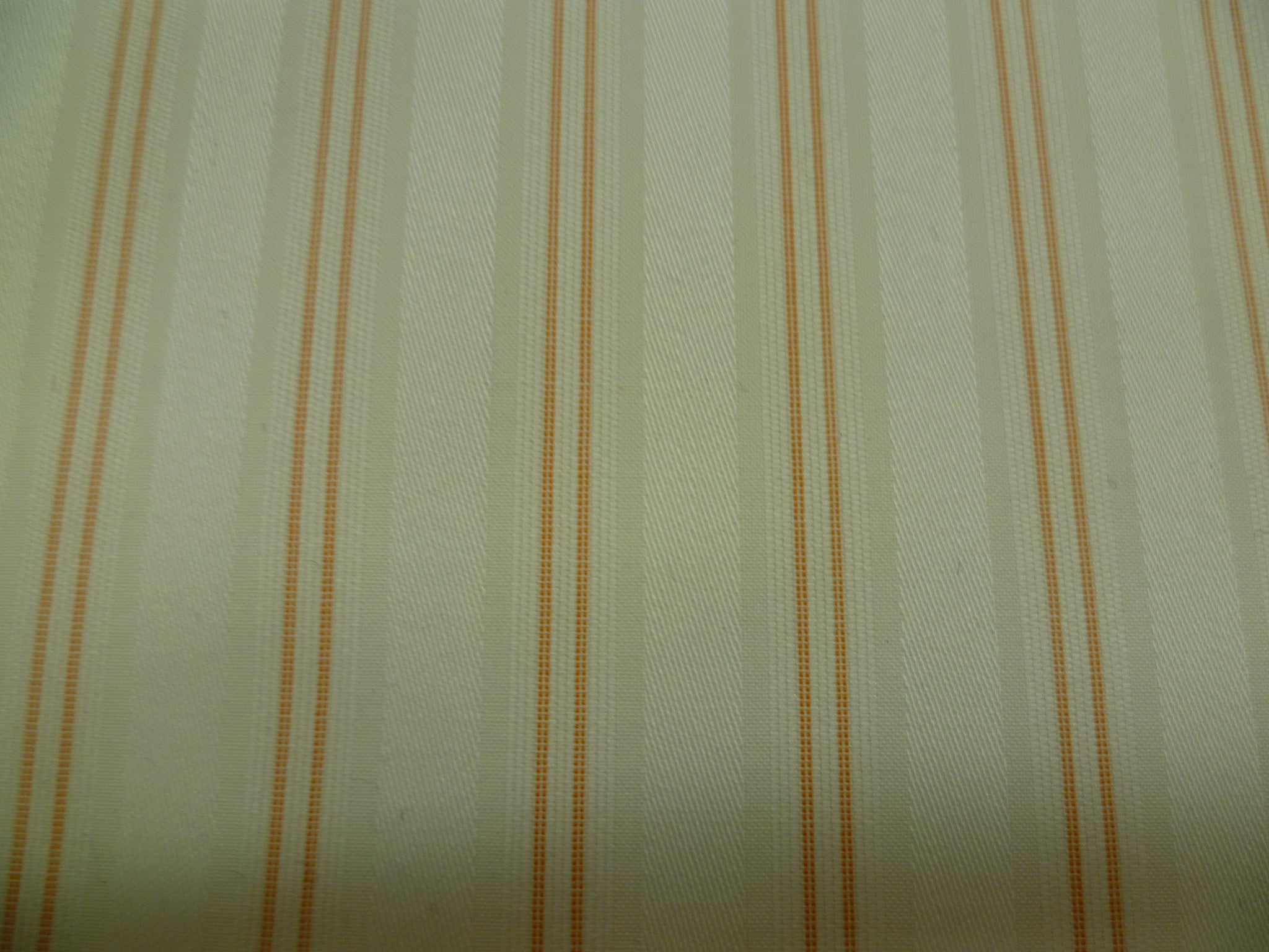 orange double pen stripe on a white background with a silky wide white stripe running through.