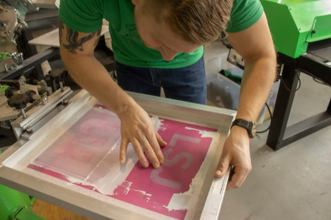 Carefully aligning the screen with ink so it can be printed properly.