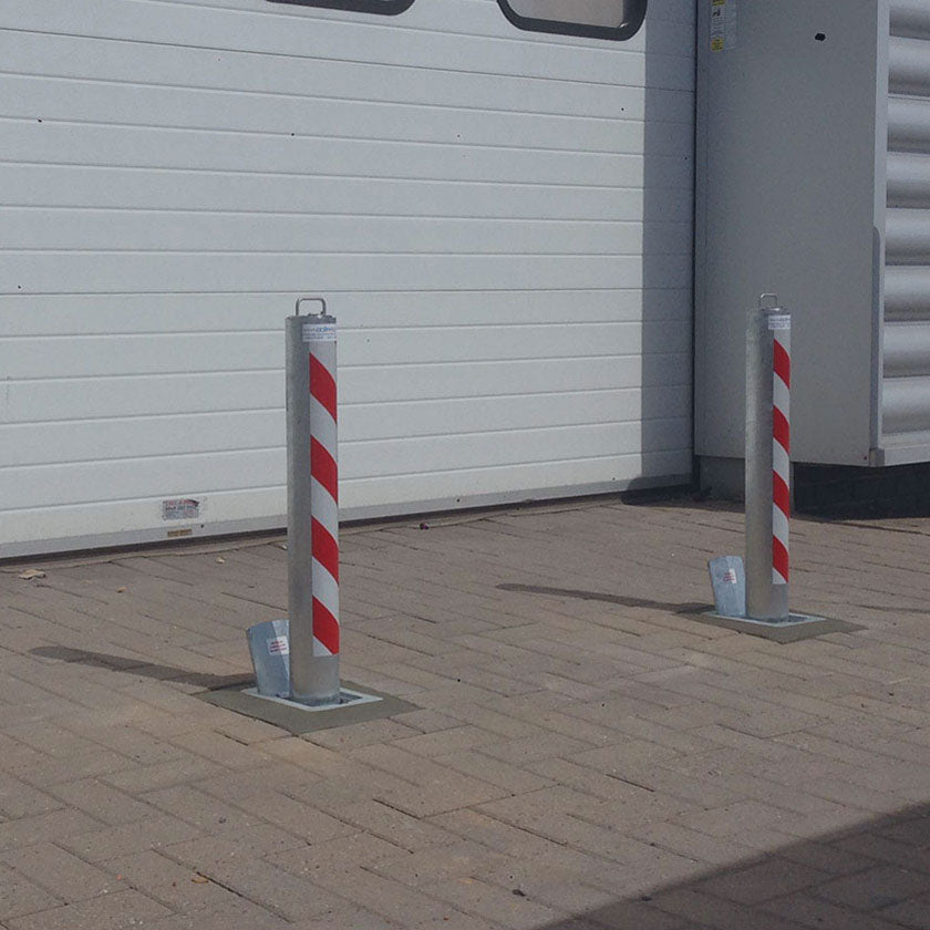 Anti-ram raid telescopic security bollards protecting roller shutters