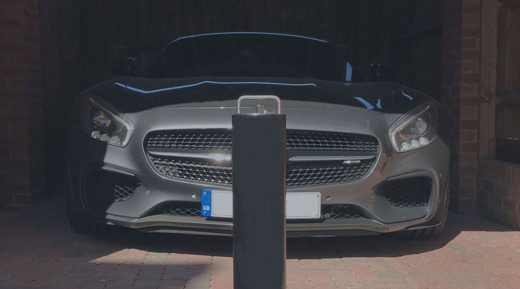 Telescopic security bollard on a private driveway protecting a Mercedes AMG sports car