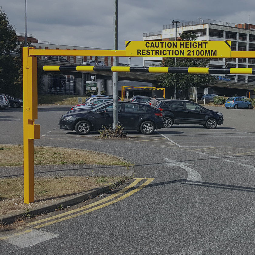 Height restriction barrier to control over height vehicles entering a retail car park.