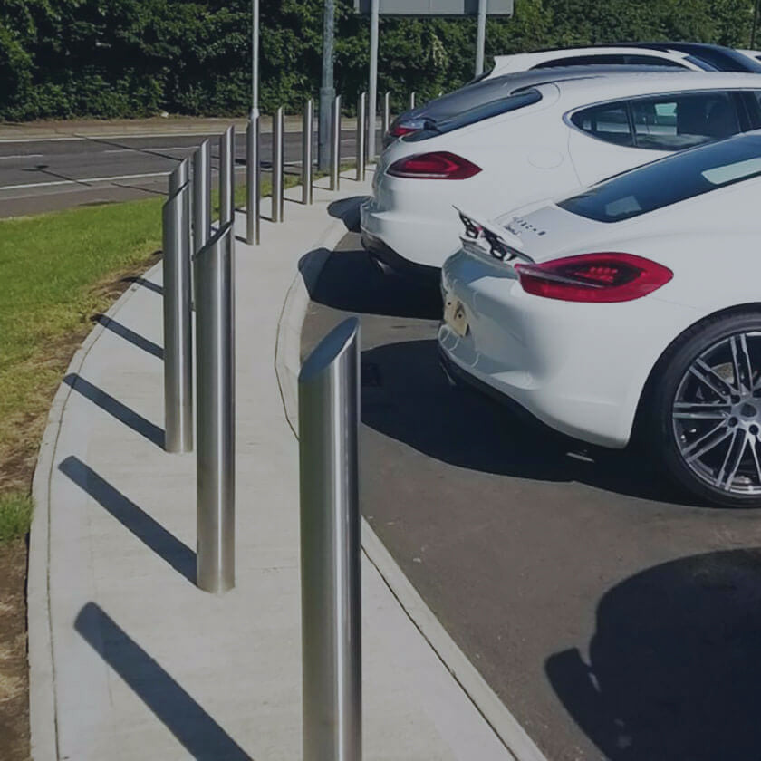 Fixed stainless steel bollards installed around the perimeter of a vehicle forecourt.