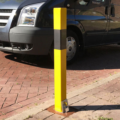 100P Removable post in Yellow with a Black band protecting a parking space.