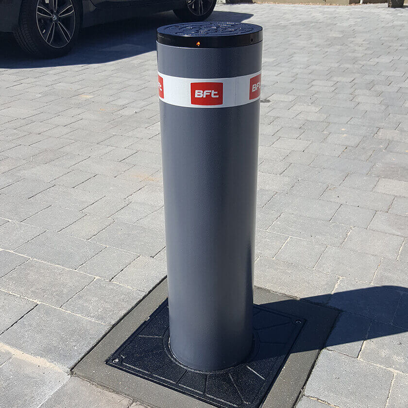 BFT Stoppy B 700  x 200mm automatic rising security bollard in a graphite grey finish, installed onto a block paved driveway