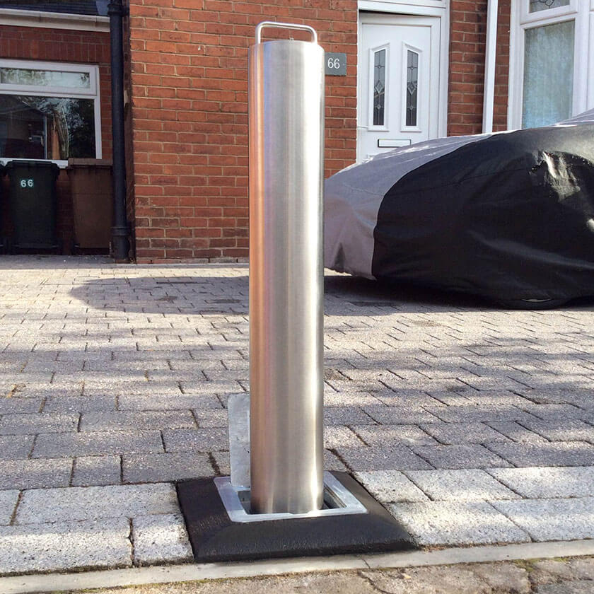 Stainless steel lift assisted telescopic bollard on a private driveway.