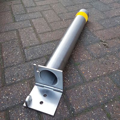 76mm diameter stainless steel fold down parking post lowered onto the ground