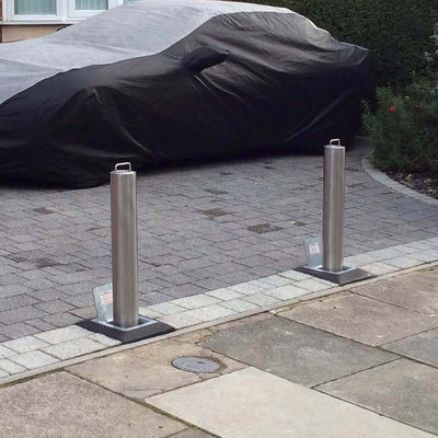 Stainless steel lift assisted telescopic bollards on a private driveway.