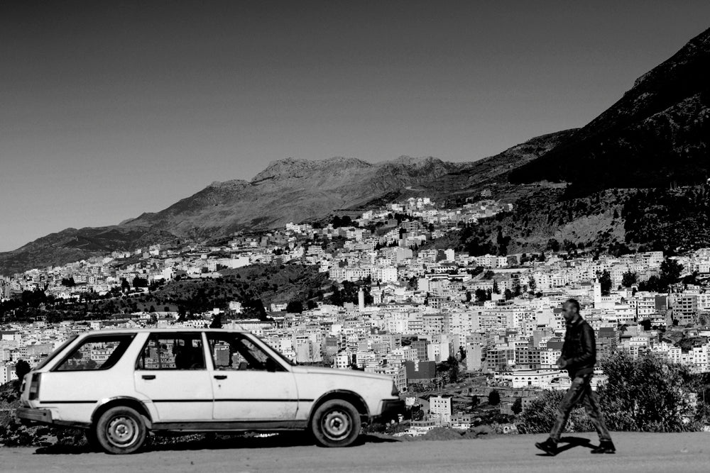 A man walks along the outskirts of Chefchaouen, Morocco with the city behind him.