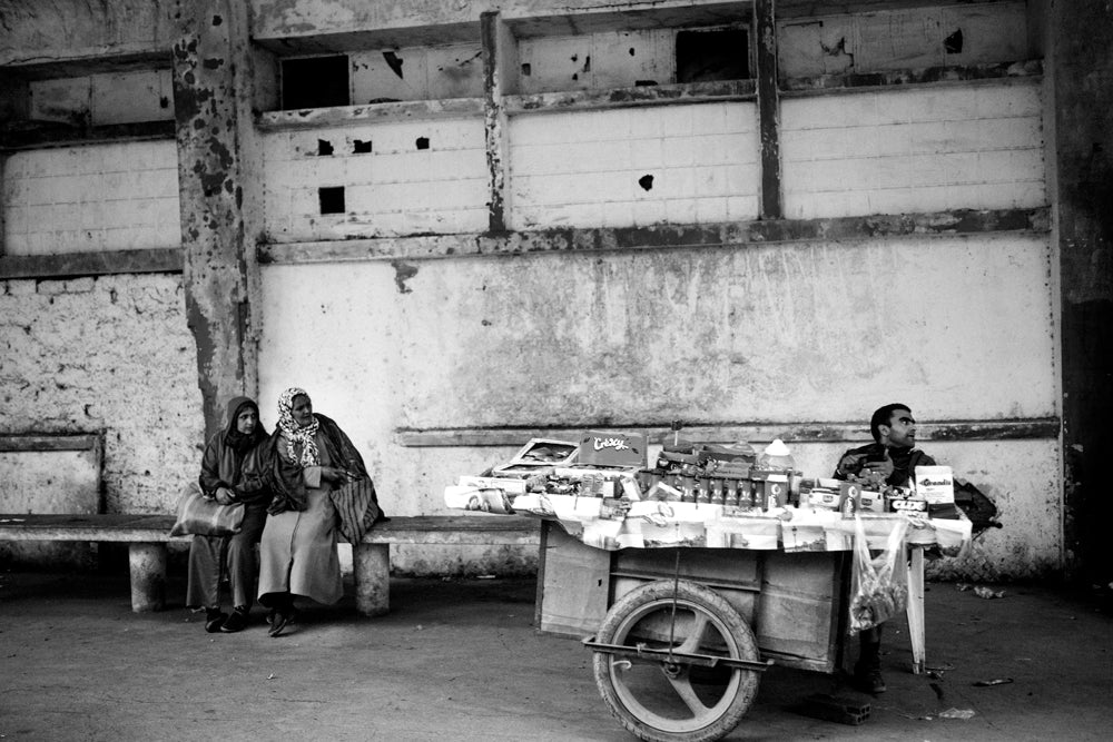 Two women on cement bench wait for bus next to a street vendor. Fez, Morocco.