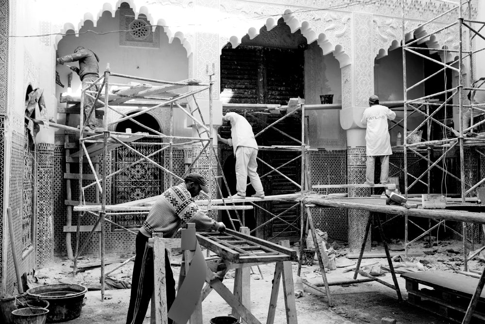 Four masonry workers stand on scaffolding while working to restore a home (traditional: riad).  Fez, Morocco.