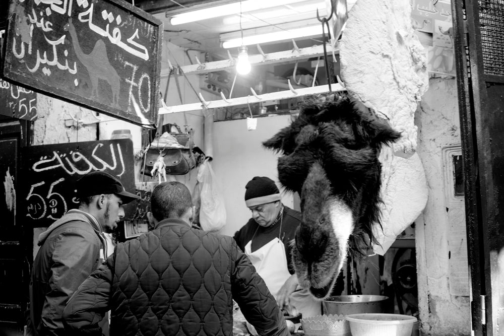 A butcher standing beside a hanging camel head serves two customers inside his shop.