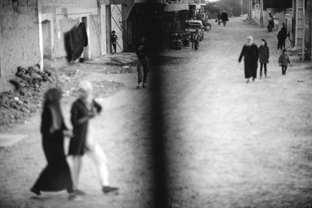 Villagers and townspeople walk in a wide street.  Image captured through a bus window while in transit to Chefchaouen.