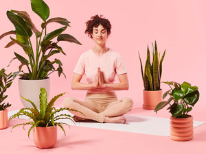 Woman Meditating Among Several Plants