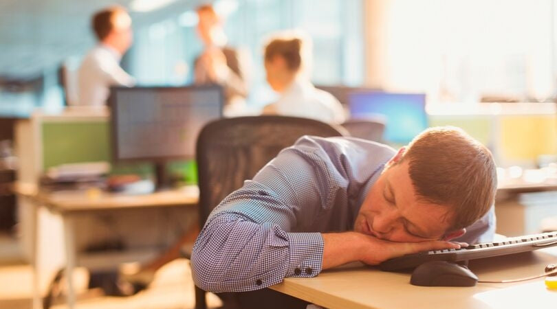 fatigue - man sleeping on his desk at work