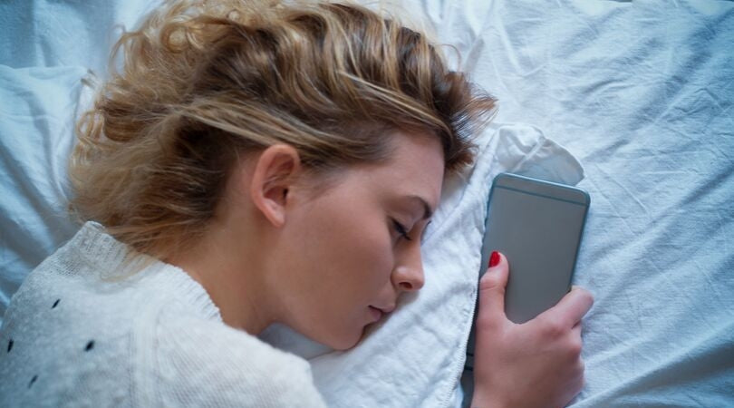 sleeping teenager holding cellphone