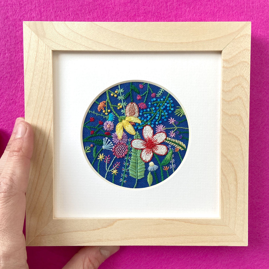 Overlapping Rainbow Flowers on Bright Blue Linen Hand Embroidered Art