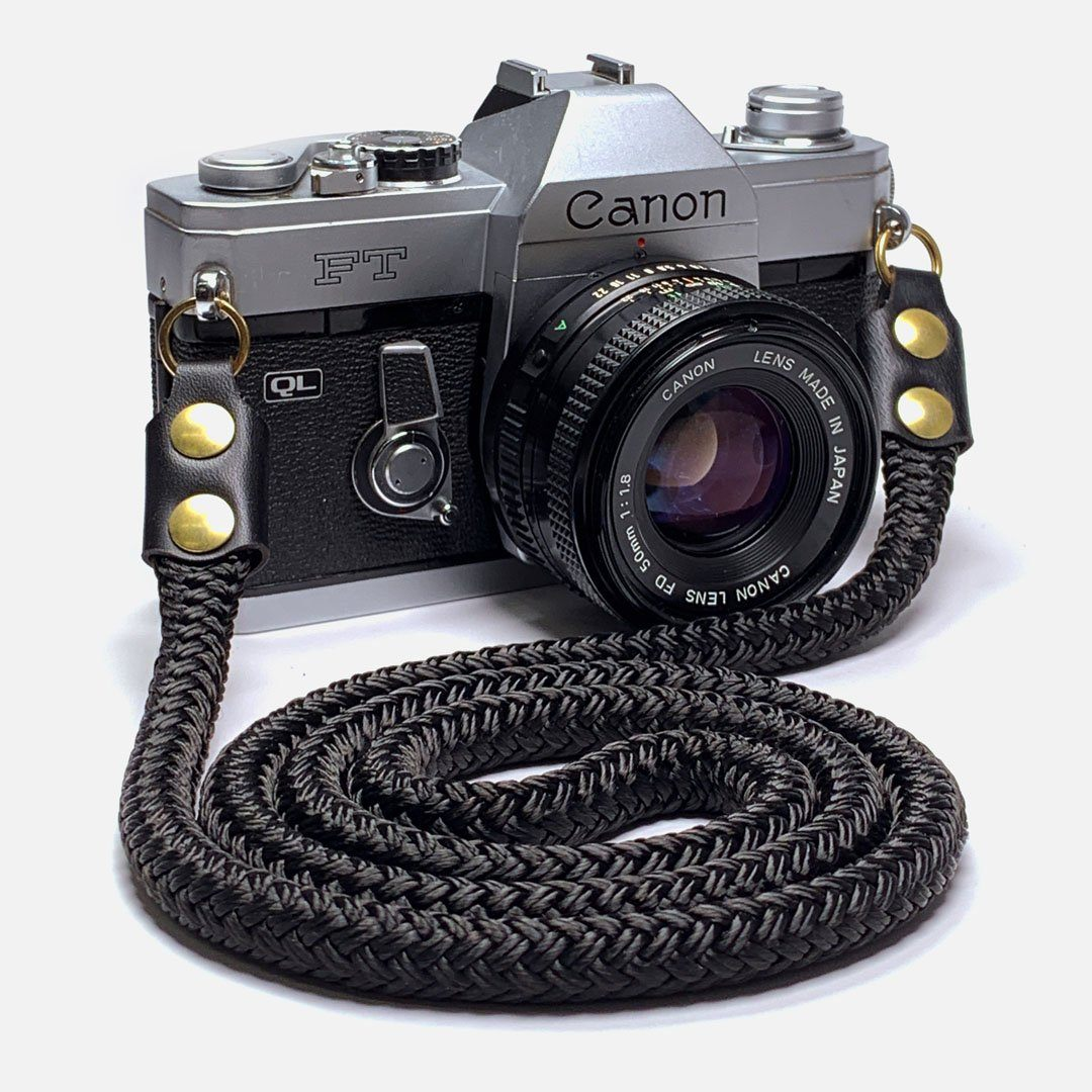 Camera Neck Strap. Black Leather, Brass and Black Nylon. Designed to hang below the chest.