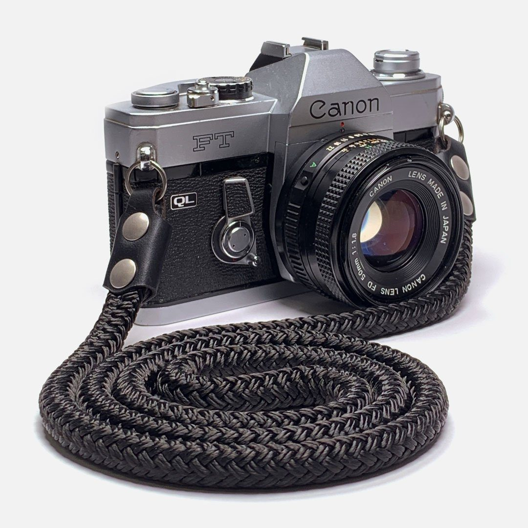 Camera Neck Strap. Black Leather, Brass and Black Nylon. Designed to hand below the chest.