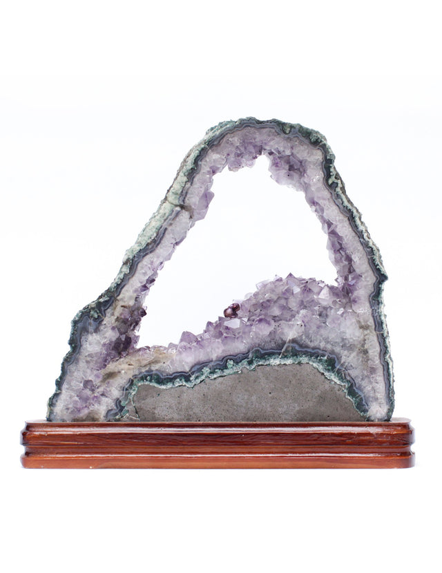 Amethyst slice with a baroque natural forming pearl on a polished wood base.