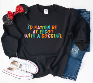 I'd Rather Be At Epcot With A Cocktail Sweatshirt. Gildan 50% cotton 50 % polyester , preshrunk, classic fit no crease, black sweatshirt with alternating colors of letters spelling I'd Rather Be At Epcot with a Cocktail . Perfect for Christmas gifts or any gift giving Disney World lover.