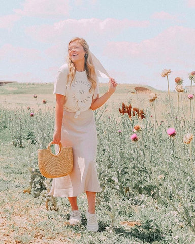 woman wearing slip skirt and relaxed tee in a flower field