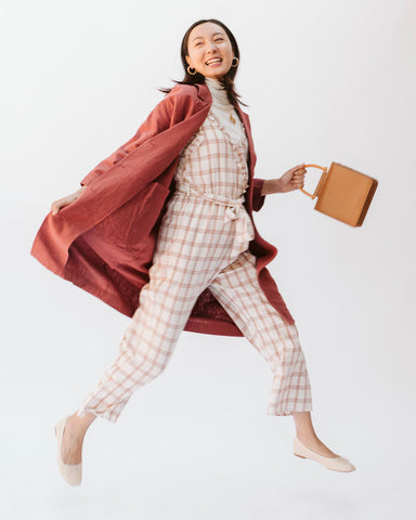 woman in plaid jumpsuit and red linen coat jumping in the air