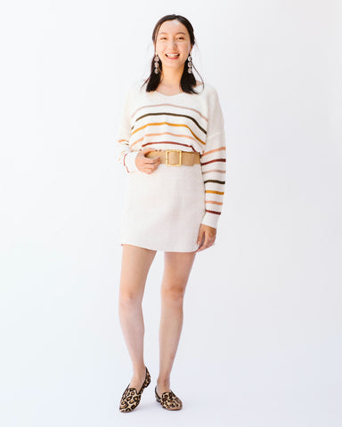 woman wearing striped sweater and tweed skirt