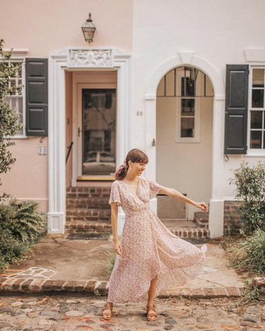 woman wearing floral wrap dress in front of quaint homes and doorways