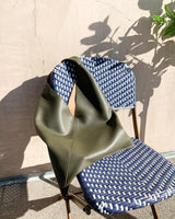 olive green minimal tote shoulder bag on blue woven chair
