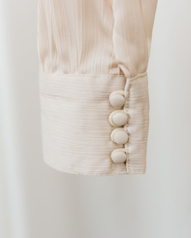 detail of buttoned cuff on knot front satin collared top