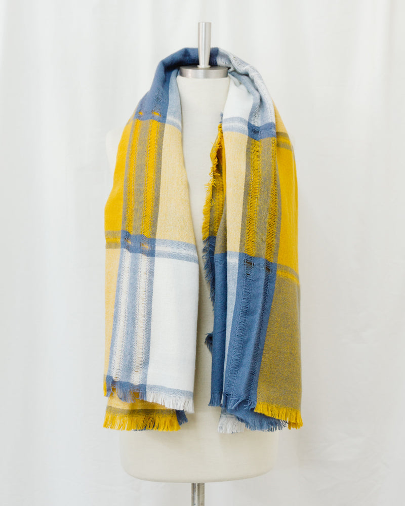 mannequin wearing yellow cream and blue plaid blanket scarf
