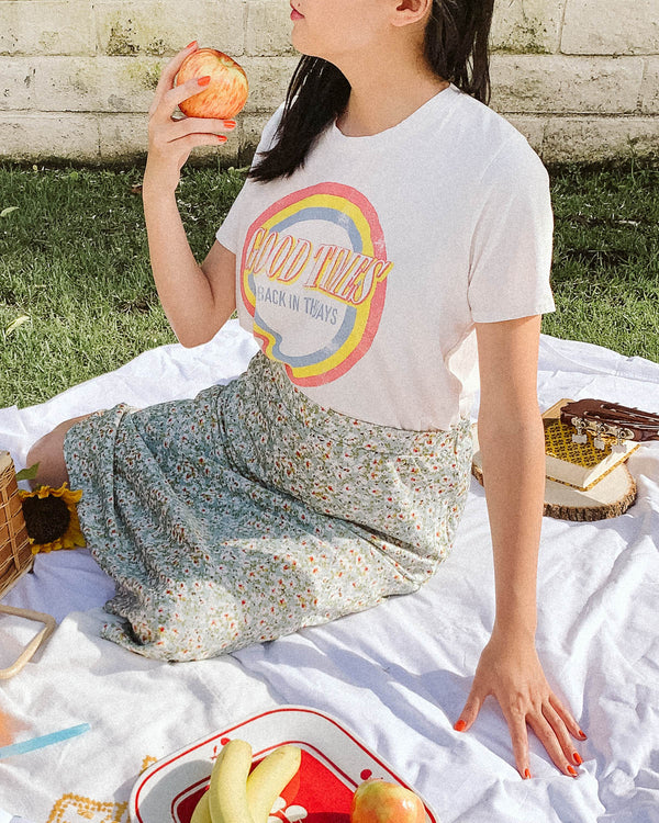 picnic setting with girl wearing graphic good times tee and floral skirt