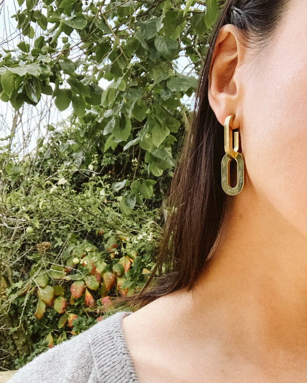 detail photo of two gold chain bold statement earrings