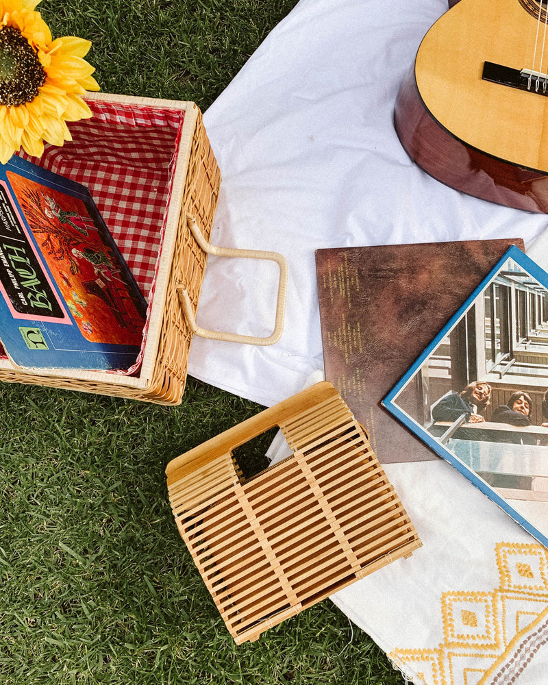 picnic flatlay with vintage records, rectangle bamboo summer rattan bag, and sunflower